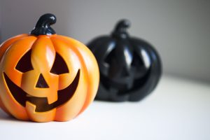 Ceramic jack-o-lantern pumpkins, one orange, one black.