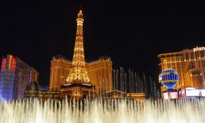 Free Bellagio Fountains shows- paris Eiffel tower in the background, lit up at night