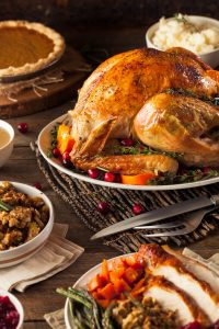 Thanksgiving turkey dinner on table with pumpkin pie