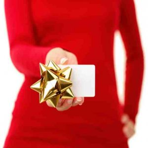 Woman in red sweater holding gift card with gold bow