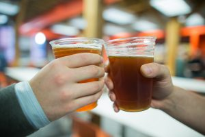 Two people cheers with draft beers in plastic cups