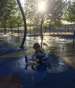 Little boy leaning over water feature at a splash pad in the sunlight