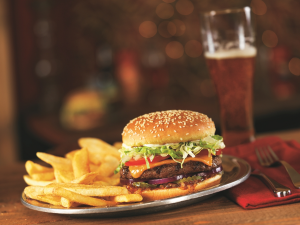 Red Robin Cheeseburger and fries on a plate, table setting with draft beer in background
