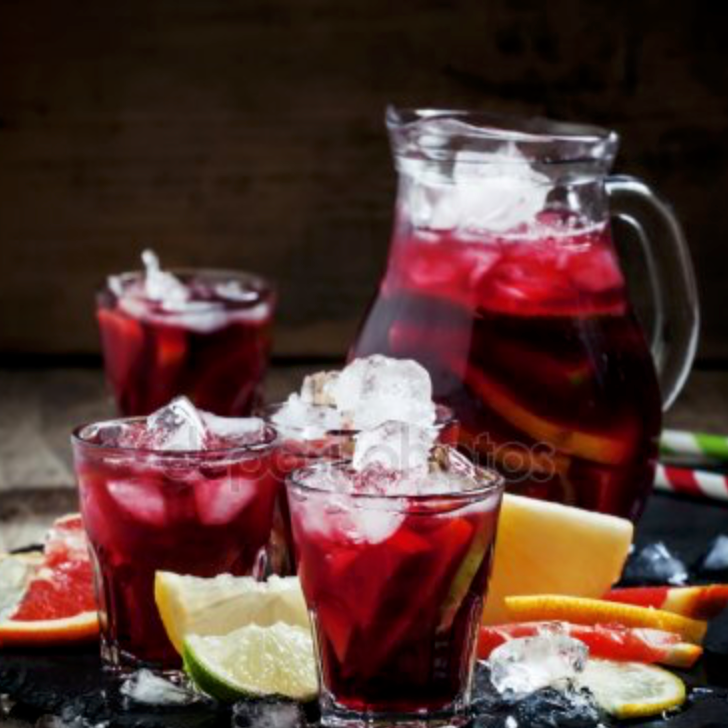 Pitcher of Sangria with three glasses and fruit all around