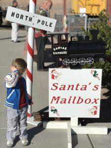 Small boy at north pole train station and santa's mailbox