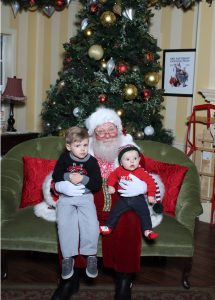 Two small boys sitting on Santa's lap for pictures