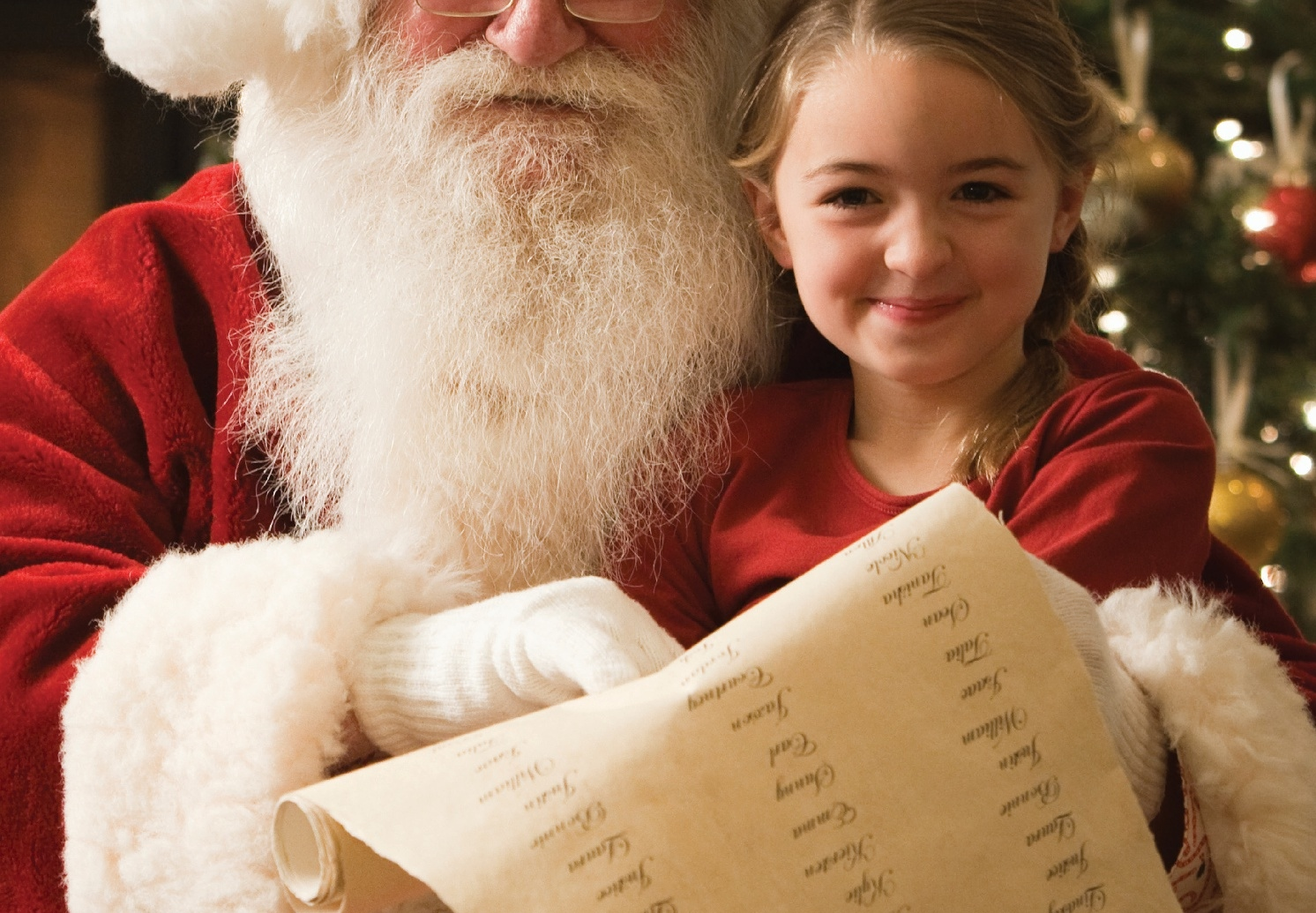Young girl on sitting with Santa and reading his list