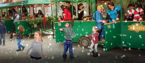 Small children playing in the snow outside of the Springs Preserve Holiday Express