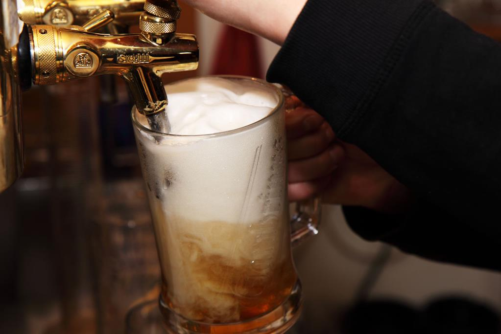 bartender pouring large draft beer from the tap