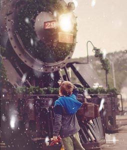 Small boy in front of Holiday train, in the snow