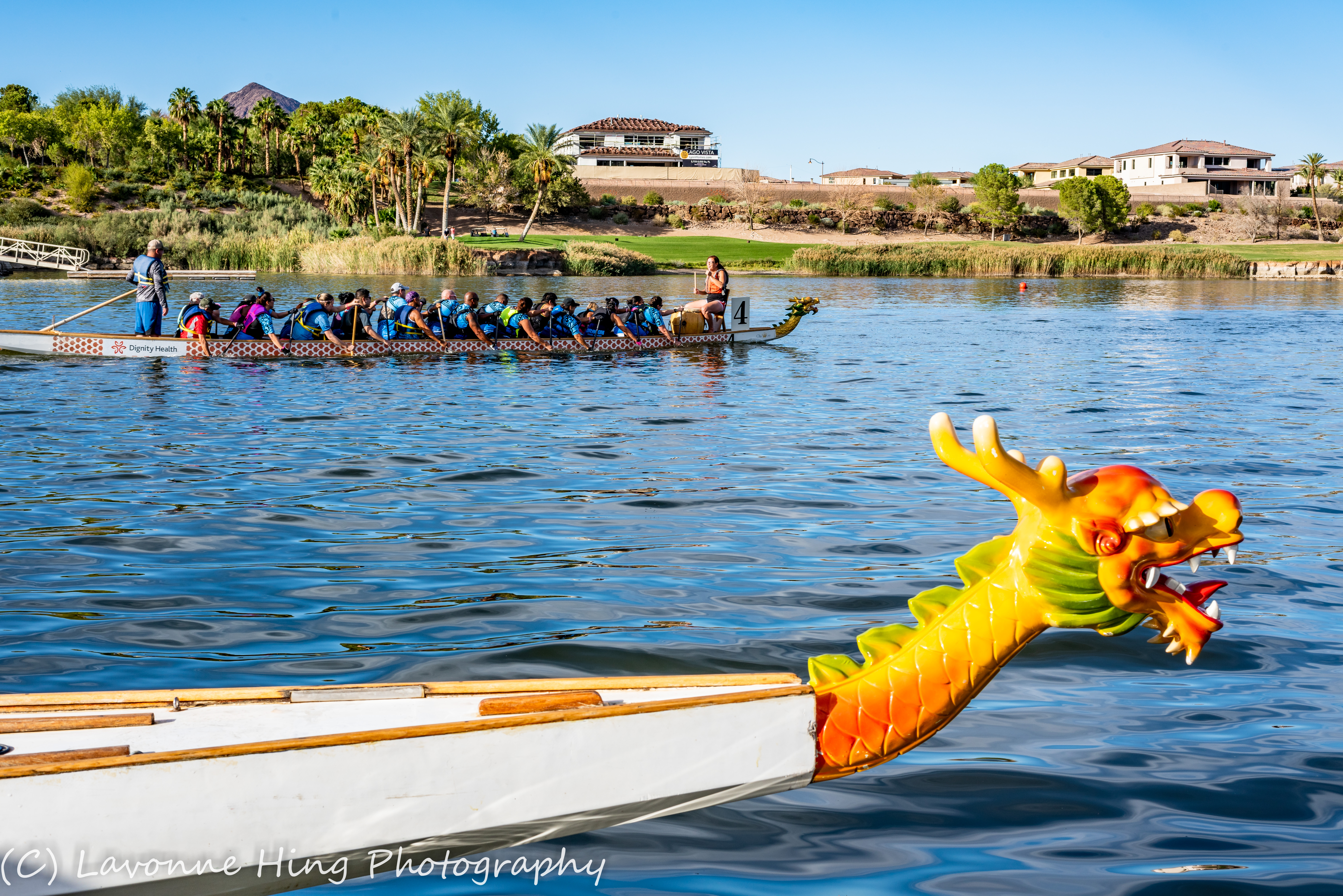 One dragon boat full of rowers on the water, and  a yellow dragon head on another boat