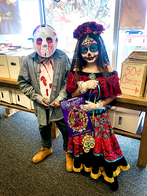 Two kids dressed in Halloween costumes in comic book shop