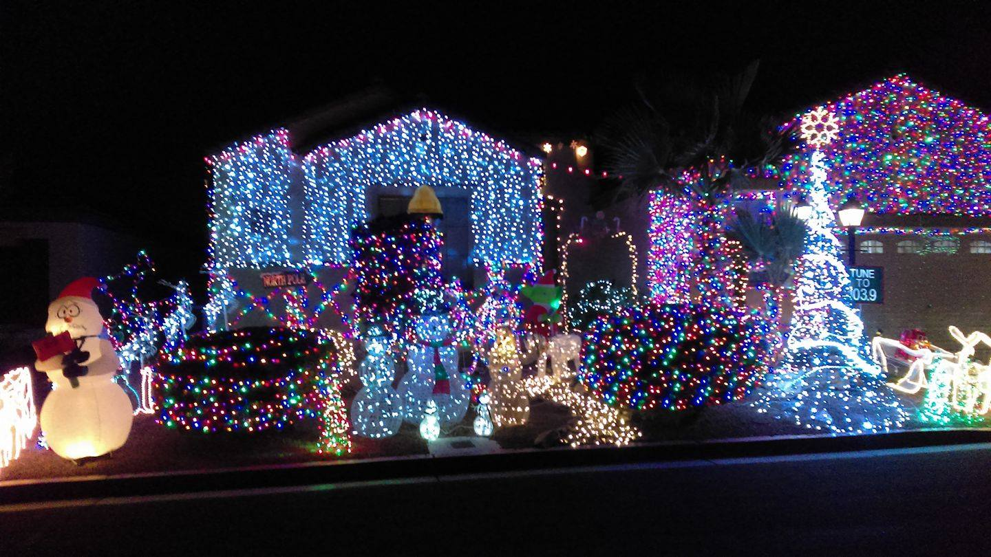 Residential home with Christmas lights covering it and inflatables