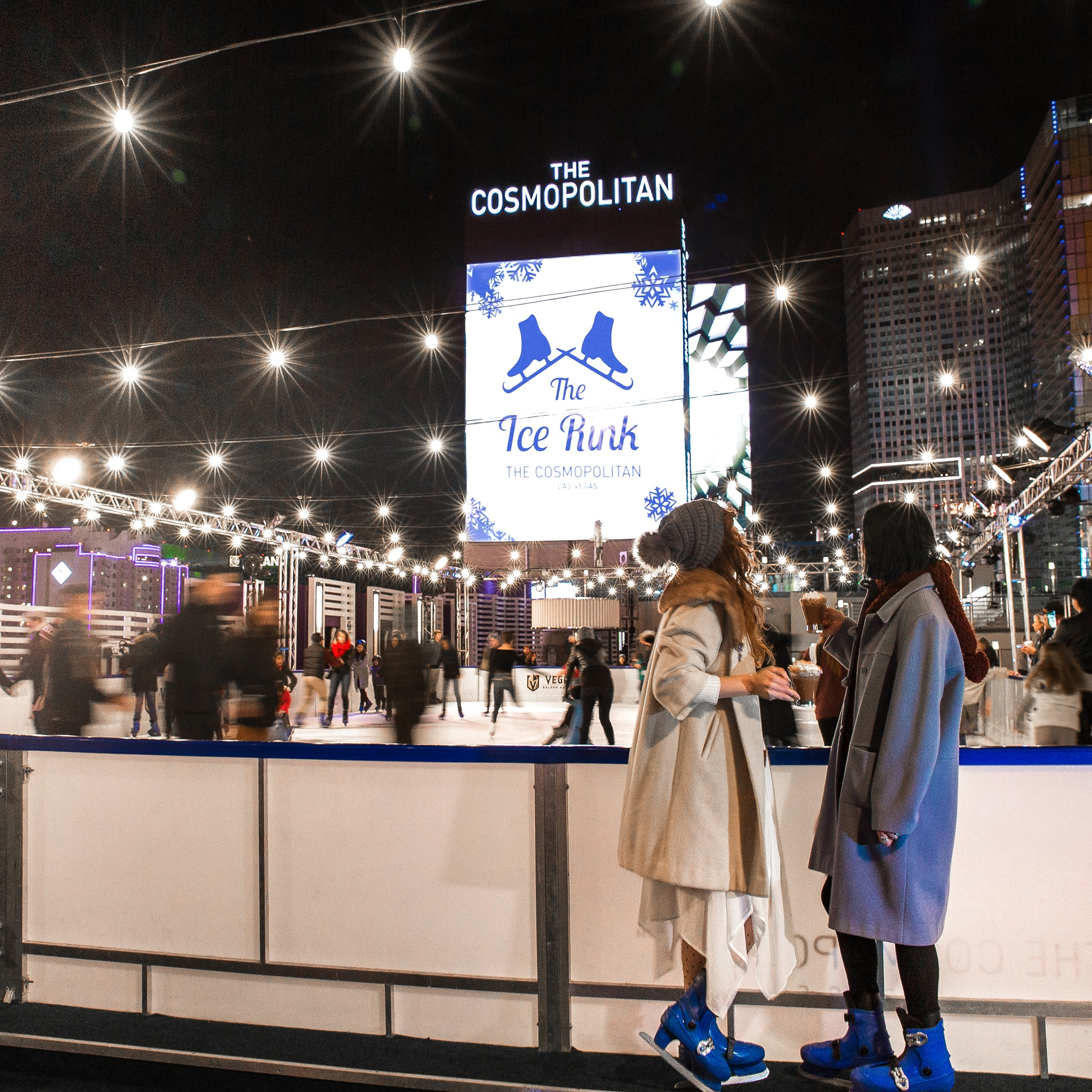 The Ice Rink at the Cosmopolitan with people skating in front of the big movie screen