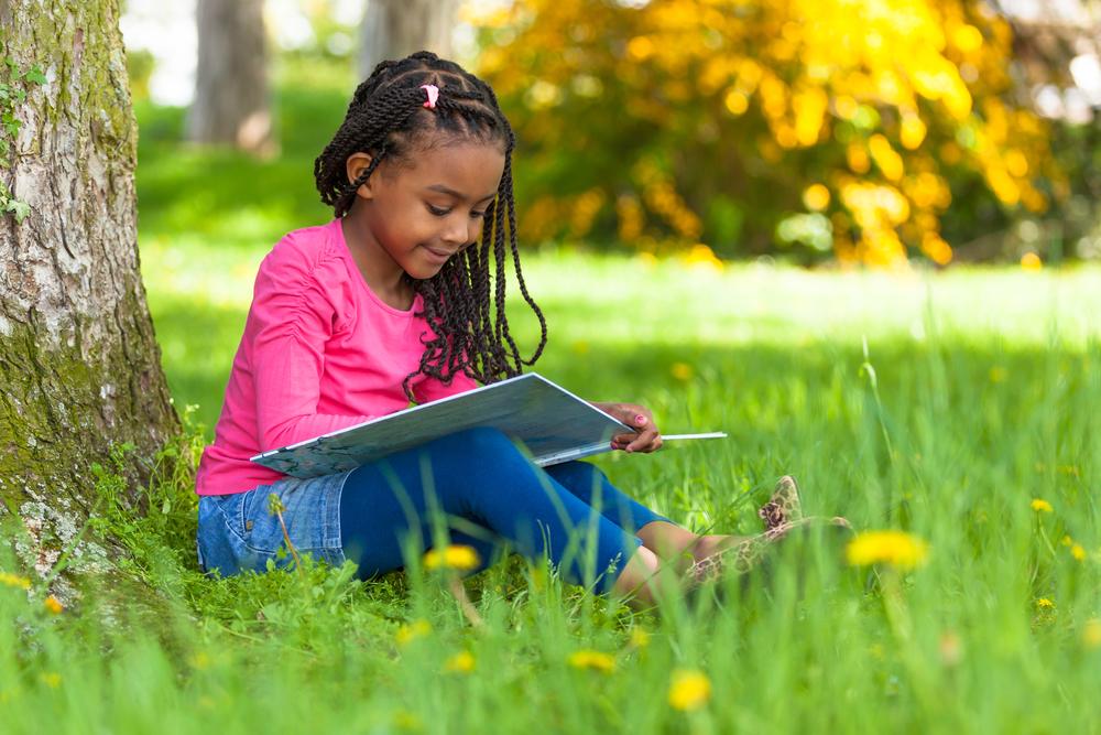 girl reading book outside spring break at home