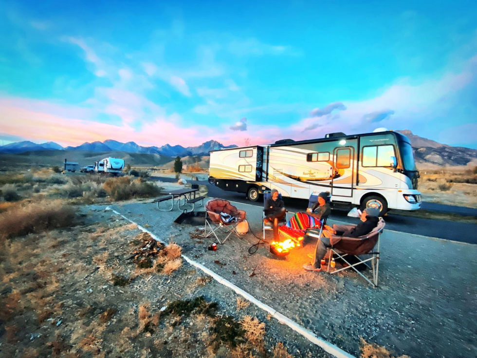 RV with campfire and friends
